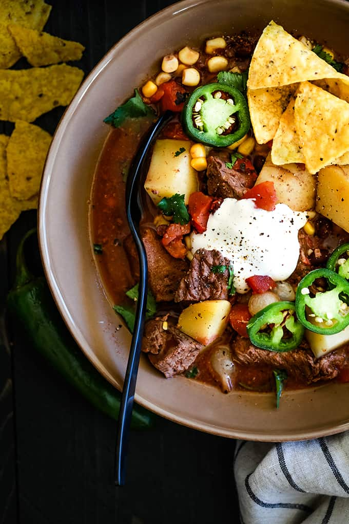 A bowl of Slow Cooker Mexican Beef Stew sits on a dark background surrounded by a striped napkin, yellow tortilla chips and a jalapeño.