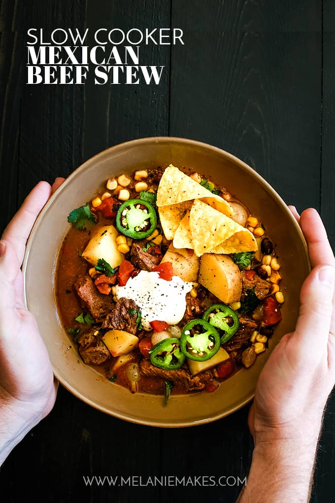 A bowl of Slow Cooker Mexican Beef Stew sits on a dark background and is held by two hands.