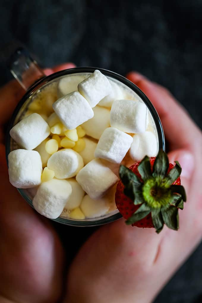 An overhead shot of two hands holding a mug of Slow Cooker Strawberry Hot Chocolate topped with marshmallows, white chocolate chips and a strawberry.