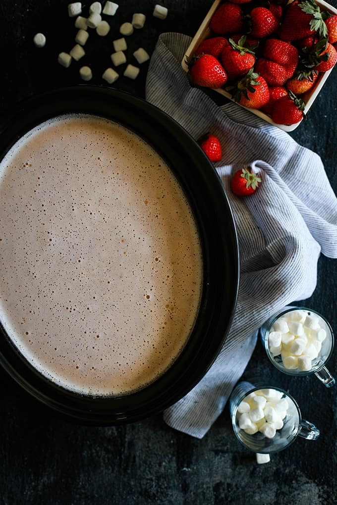 A slow cooker full of Slow Cooker Strawberry Hot Chocolate surrounded by marshmallows, a pint of strawberries and a striped napkin on a dark surface.