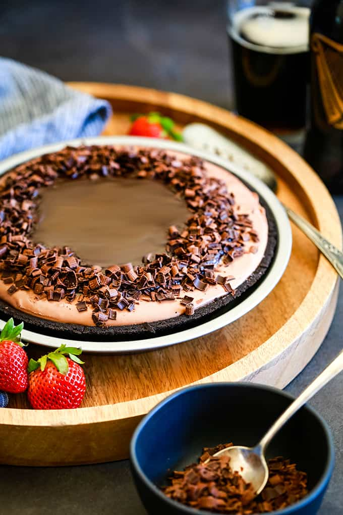 A No Bake Guinness Chocolate Cheesecake on a wooden tray with a pie server and strawberries.
