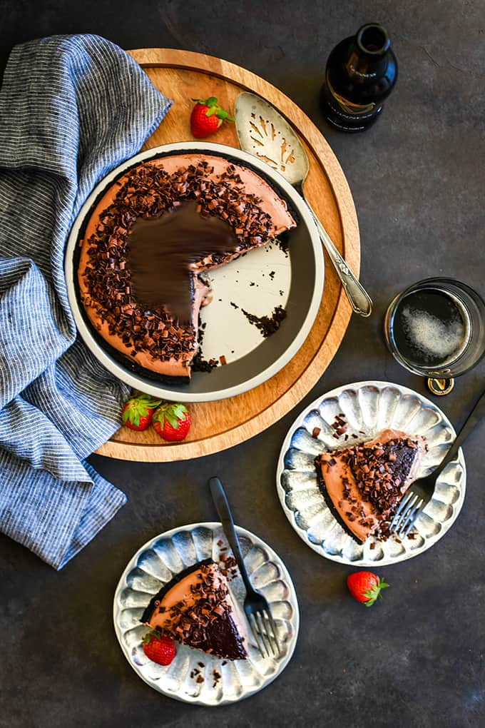 An overhead view of a No Bake Guinness Chocolate Cheesecake sitting on a wooden tray with two slices removed and sitting on silver plates.