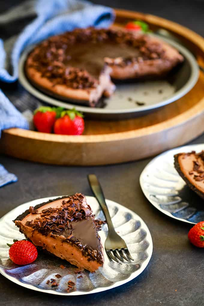 A slice of No Bake Guinness Chocolate Cheesecake sits on a silver plate with a black fork and strawberry.