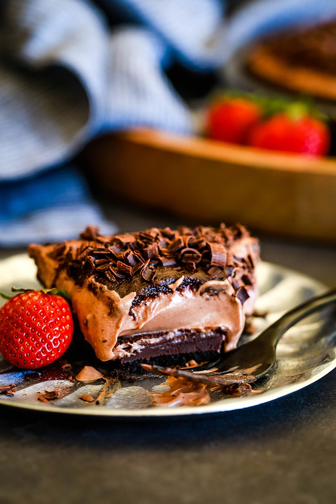 A slice of No Bake Guinness Chocolate Cheesecake sits on a silver plate with a bite removed.