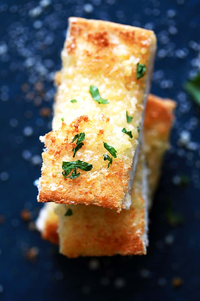 This six ingredient Parmesan Garlic Bread is ready to become a mainstay in your kitchen.  A loaf of French bread from your grocery store's bakery is halved and then topped with a mixture of olive oil, butter, garlic and grated Parmesan cheese and then showered with chopped fresh parsley.