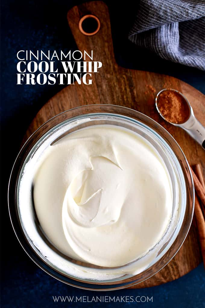 A bowl of Cinnamon Cool Whip Frosting sits on a wood serving board.