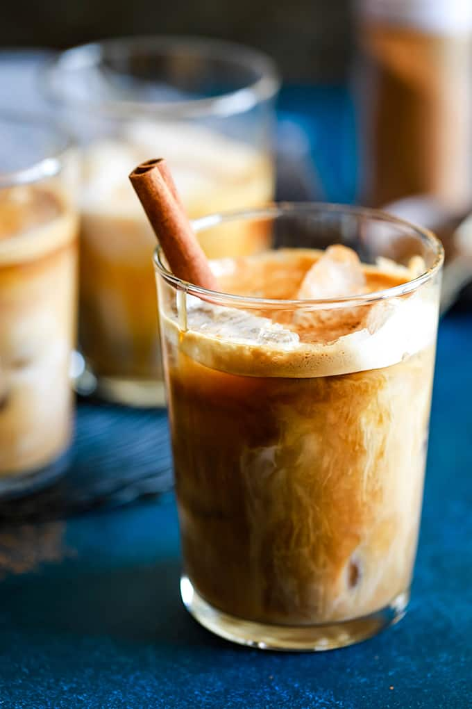 An Iced Cinnamon Almond Milk Macchiato with a cinnamon stick in front of two other glasses.