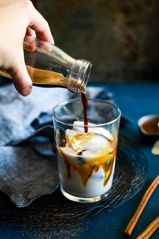 A hand pouring espresso into an Iced Cinnamon Almond Milk Macchiato.