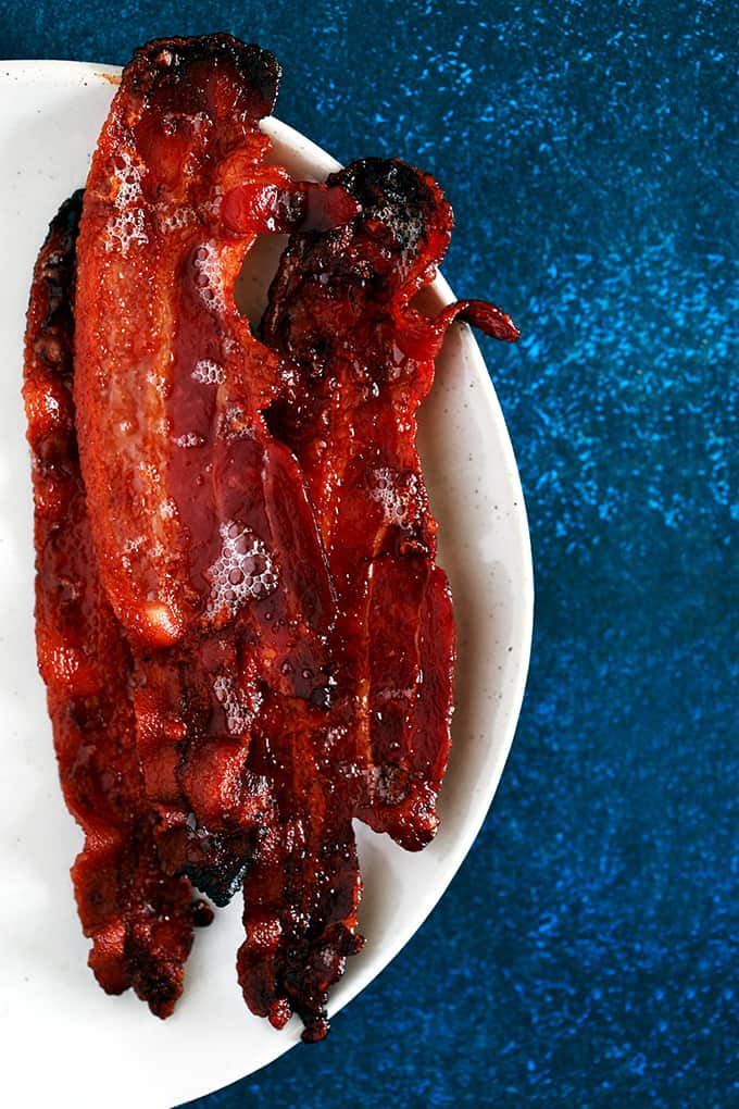 Four slices of Oven Roasted Bacon sit on a white plate on a dark blue background.