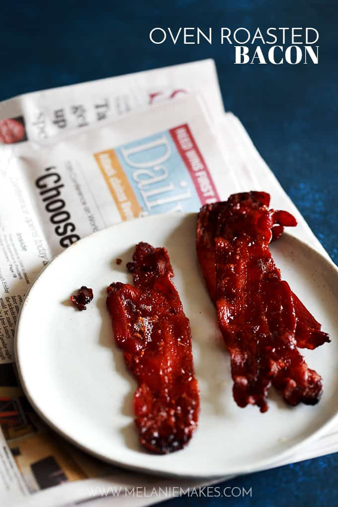 Two pieces of Oven Roasted Bacon sit on a white plate on a folded newspaper.