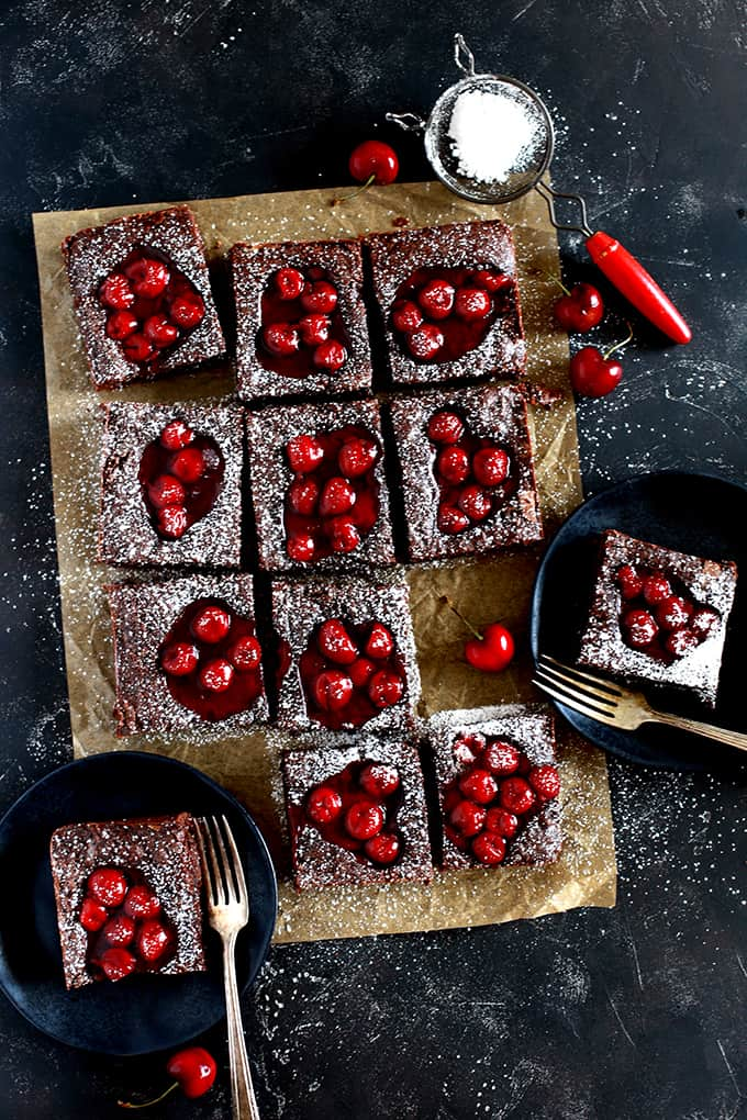 Fudgy Black Forest Bars sit on a brown parchment square on a black background. Two bars are on black plates with forks and powdered sugar rests in a sifter.