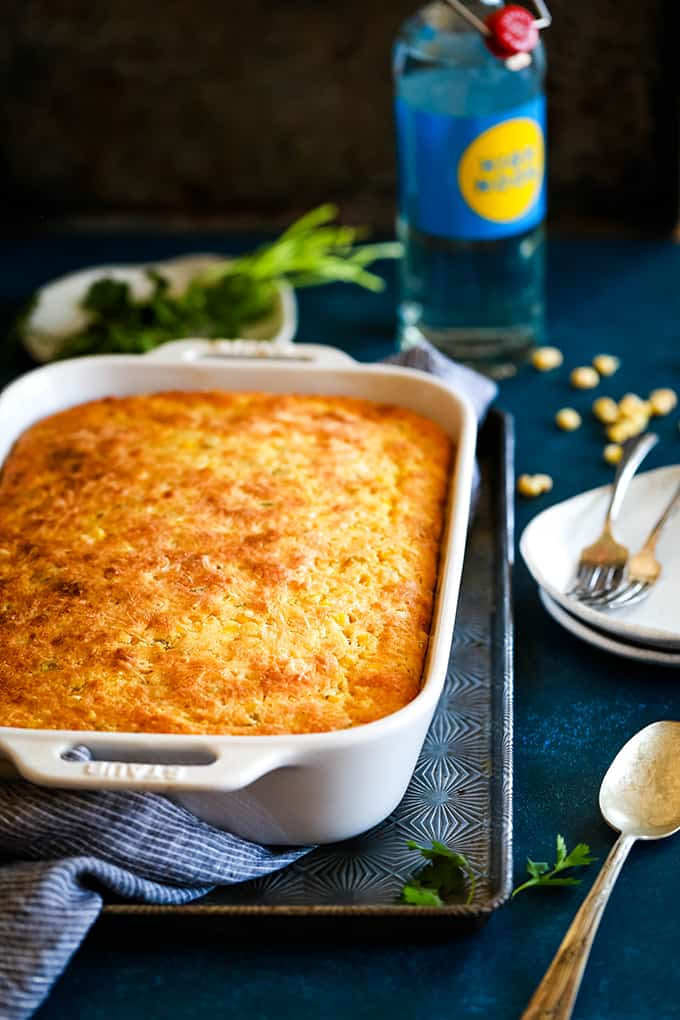 A Southwest Green Chile Corn Casserole surrounded by plates and silverware.