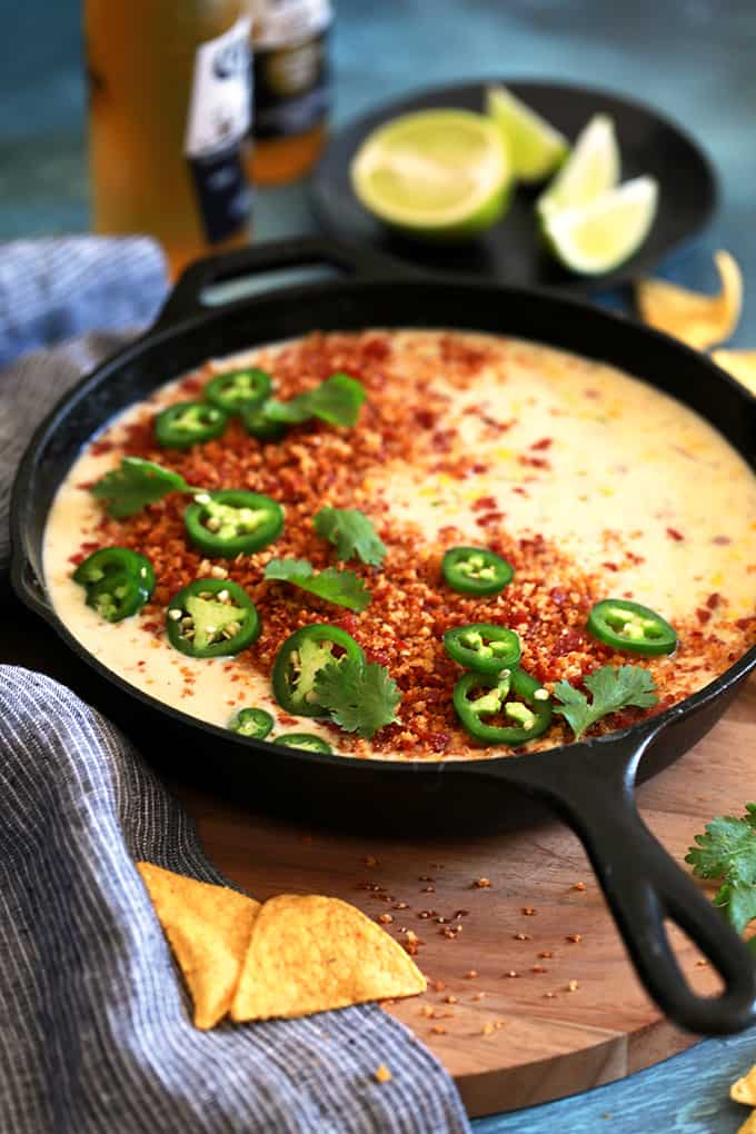 This Sweet Corn Queso with Pepperoni Crumbs literally comes together by just stirring ingredients together with a spoon in a cast iron skillet.  Red onion, garlic, jalapeño and corn are stirred into Monterey Jack cheese to create this incredible queso that's garnished with the most insanely delicious pepperoni crumbs, cilantro and jalapeños.