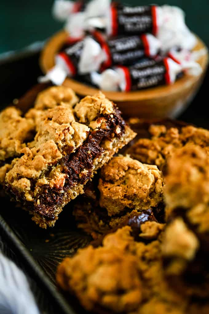 Tootsie Roll Bars on a baking sheet with a wooden bowl of Tootsie Roll candy.