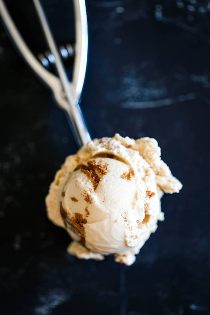 A silver ice cream scoop with a scoop of Biscoff Cookie Butter Ice Cream.