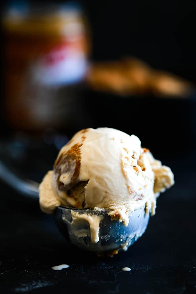 A melting scoop of Biscoff Cookie Butter Ice Cream in a silver ice cream scoop.