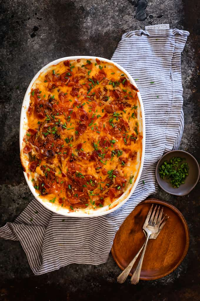 Loaded Scalloped Potatoes on a black and grey background with a striped towel, wooden plates, silverware and a small dish of chives for garnish.