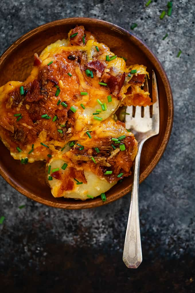 A serving of Loaded Scalloped Potatoes on a wooden plate with a fork on a black and grey background.