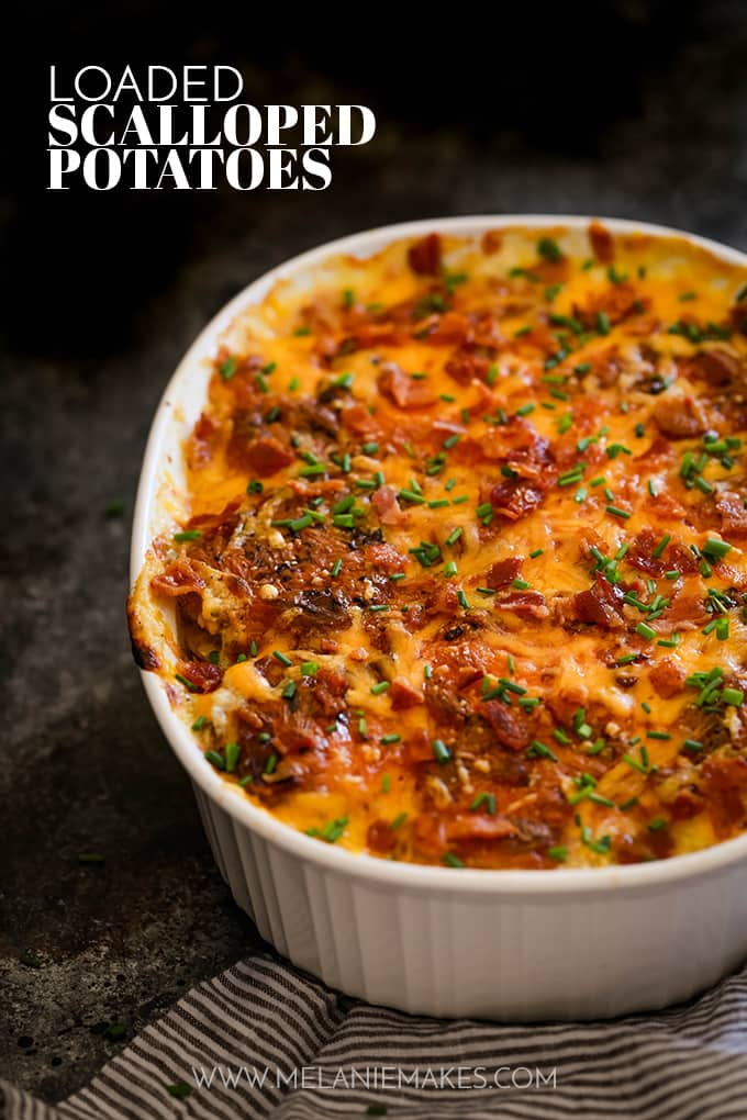 Loaded Scalloped Potatoes in a white casserole dish on top of a striped towel.
