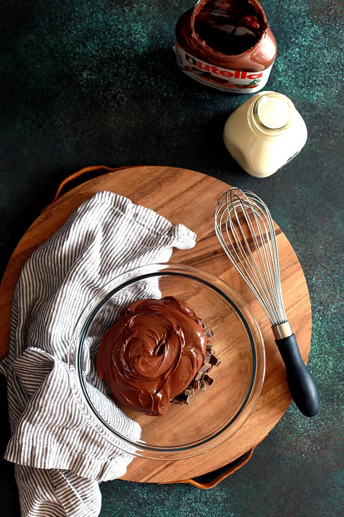 An overhead shot of a bowl of Microwave Nutella Ganache sitting on a wooden tray flanked by a striped napkin and whisk on a speckled surface.