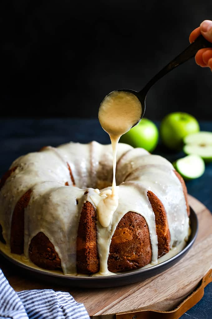 An Apple Cream Cheese Bundt Cake is being drizzled with caramel icing on a plate sits atop a wood serving board flanked by a striped towel and green apples.