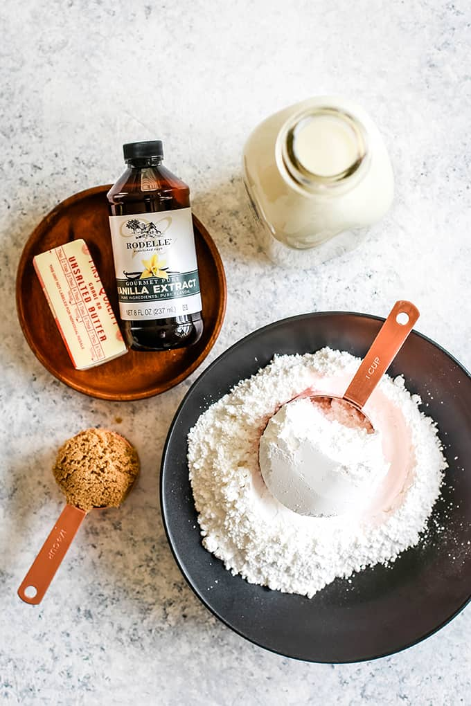 All of the ingredients needed to make Homemade Caramel Icing on a speckled background.