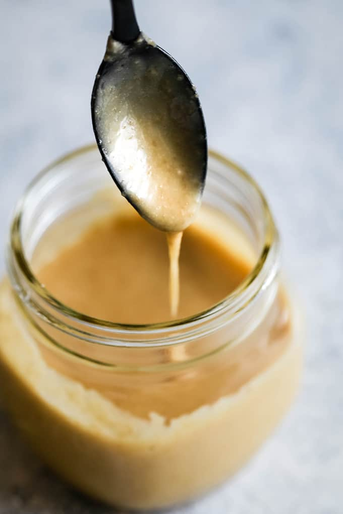 A black spoon with Homemade Caramel Icing drizzles icing into a glass jar full of icing.