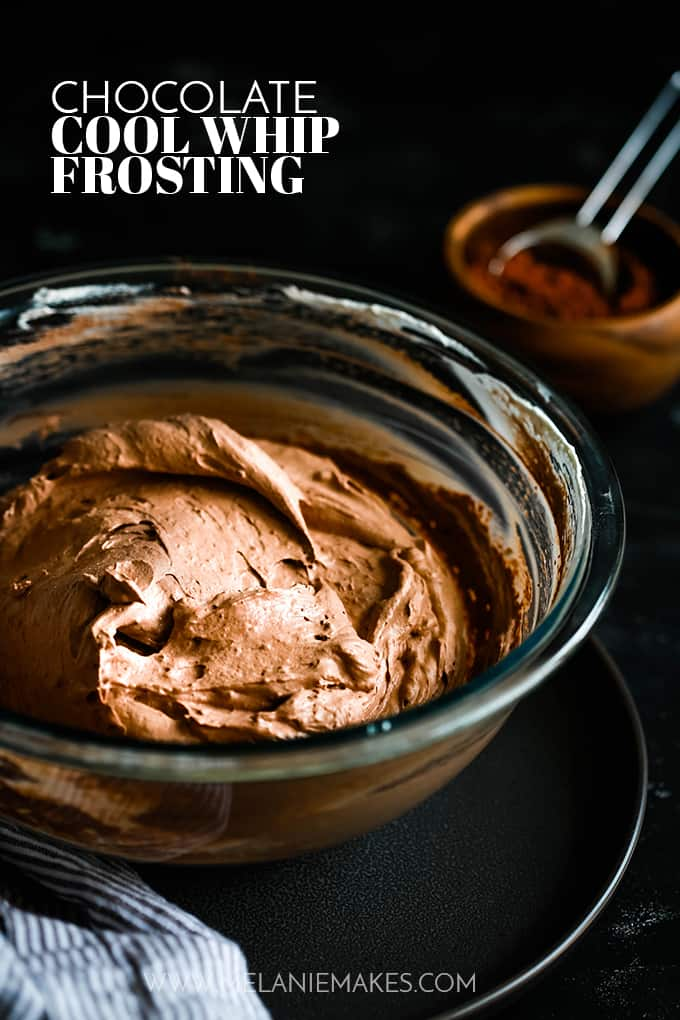 A bowl of Chocolate Cool Whip Frosting sits on a dark tray with a striped napkin to the side and a small wooden bowl with cocoa powder sits to the right.
