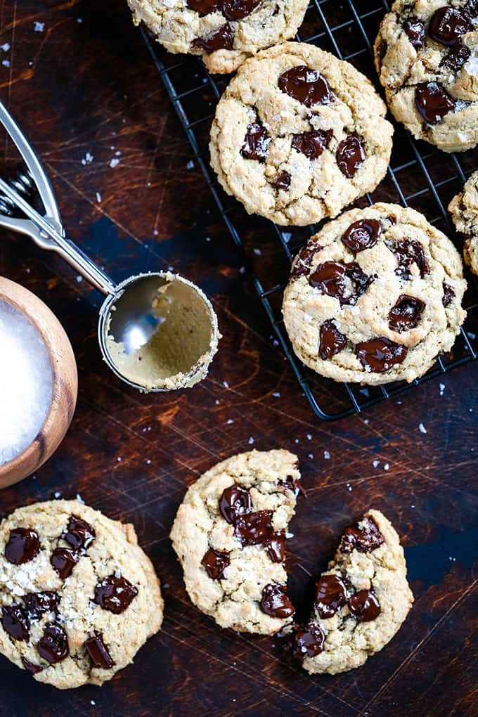 Salted Chocolate Chunk Cookies sit on a cooling rack and on a dark surface surrounded by a bowl of sea salt and a cookie scoop.