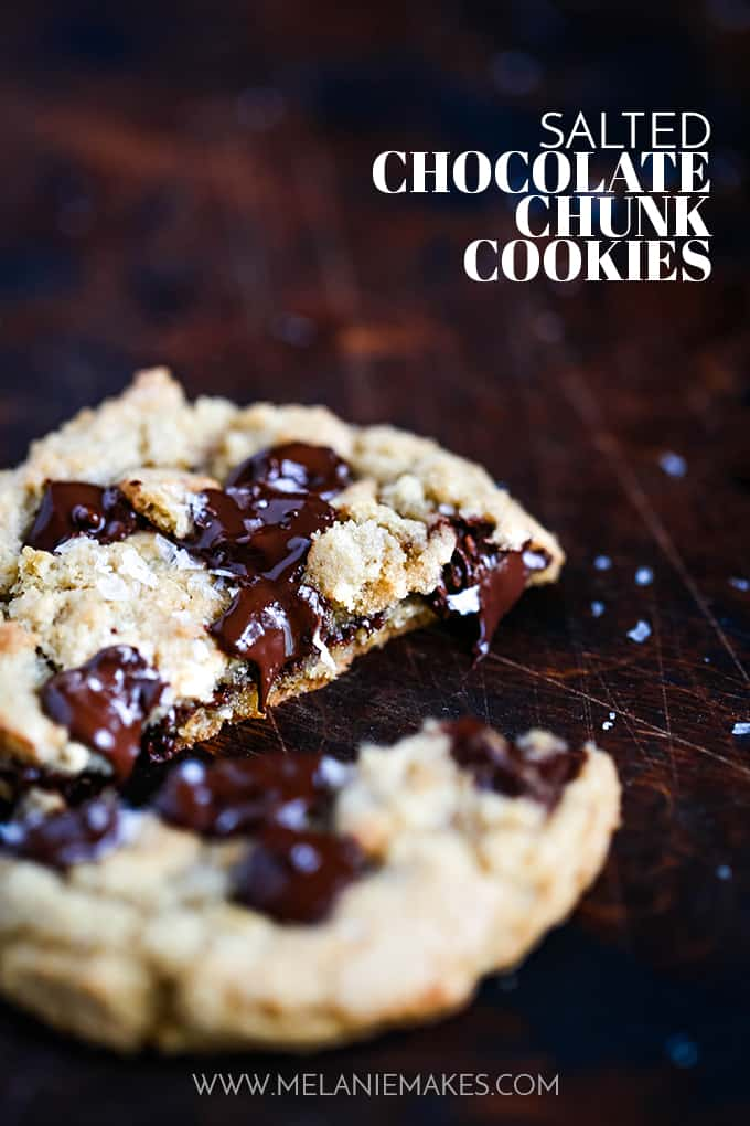A Salted Chocolate Chunk Cookie is split in half on a dark surface.