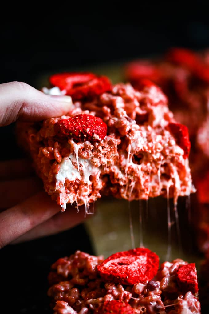 A hand holds a Strawberry Rice Krispie Treat.