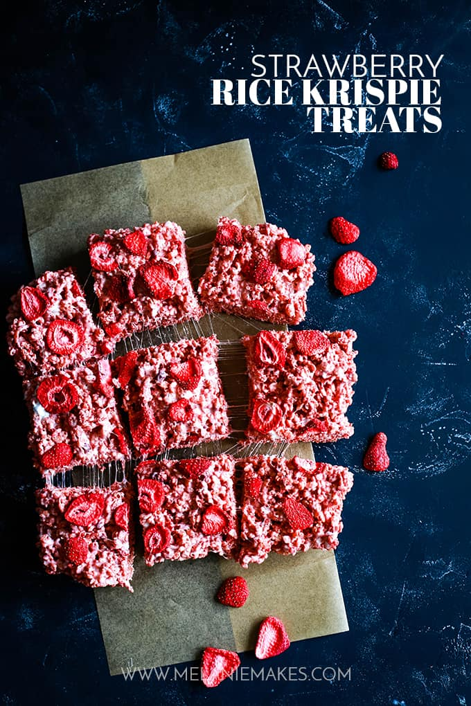 Strawberry Rice Krispie Treats cut and laying on a dark surface.
